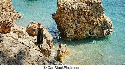 Young woman in black dress standing on the rocks