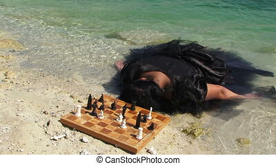 Young Woman In Black Dress With Board Of Chess Near Lake
