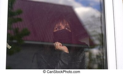 Young woman in black medical mask looking out window being ...
