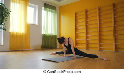 Young woman in black practicing stretching, fitness or yoga...