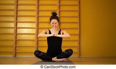 Young woman in black practicing yoga at light minimalist...