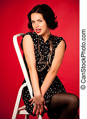 Young woman in black vintage dress sitting on chair over red background