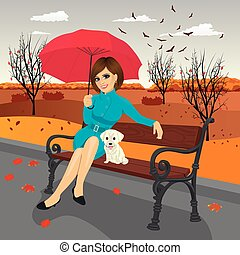 young woman in blue autumn coat holding red umbrella sitting on a bench with labrador puppy in city park on a rainy day