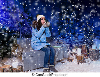 Young woman in blue down jacket blows snowflakes while sitting on a swing with a blanket in the evening in a snow-covered park with spruce trees