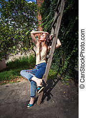 young woman in blue jeans and high heels in backyard summer fashion