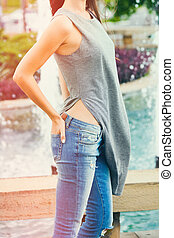 young woman in blue jeans summer day in city close up side view