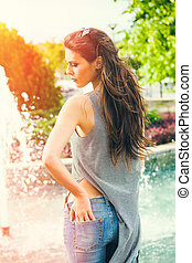 young woman in blue jeans summer day in city