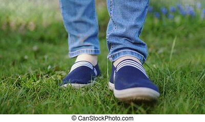Young woman in blue sneakers goes on a meadow in slow motion...