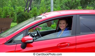 Young woman in blue suit drives red car. She stoppes and...
