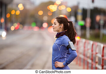 Young woman in blue sweatshirt running in the city