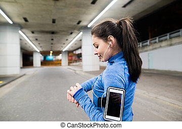 Young woman in blue sweatshirt running in the night town -...