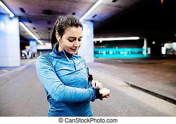 Young woman in blue sweatshirt running in the night town - ...