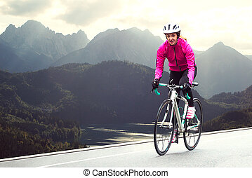 Young Woman in Bright Pink Jacket Riding Road Bicycle on Mountain Alpine Road. Healthy Lifestyle and Adventure Concept.