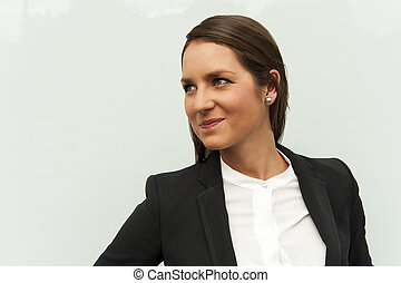 Young woman in business outfit looking left, in the city by the glass wall smiling.