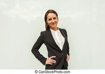 Young woman in business outfit over the glass wall in the city smiling at camera.