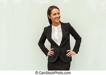 Young woman in business outfit over the glass wall in the city smiling.