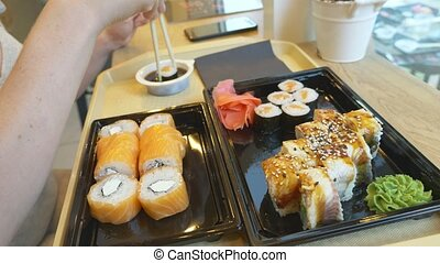 Young woman in cafe eating sushi with chopsticks. 4k,...