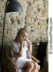 Young woman in cafe with mobile phone
