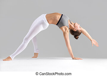 Young woman in Camatkarasana pose, grey studio background -...