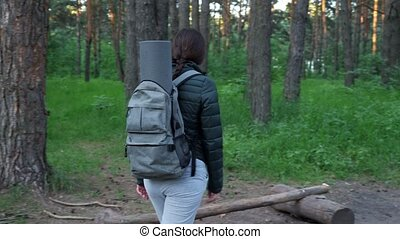 Young woman in camping clothes and with a backpack stops in the forest