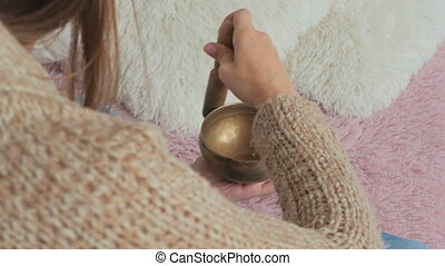 Young woman in cardigan relaxing with nepal singing bowl -...