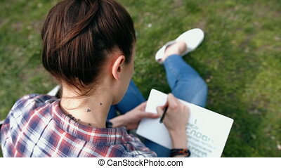 Young woman in casual clothes with tattoo on neck writing in her journal sitting on grass in the park, view from behind