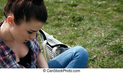 Young woman in casual clothes writing in her journal sitting...