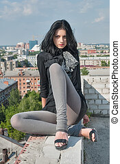 Young woman in casual sitting on roof