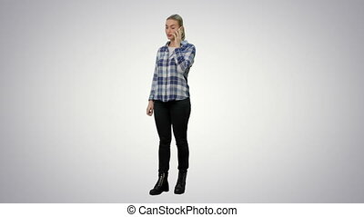 Young woman in casual talking gossips via cellphone on white background.