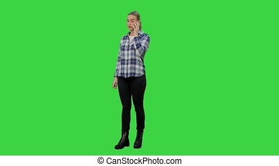 Young woman in casual talking gossips via cellphone on a Green Screen, Chroma Key.