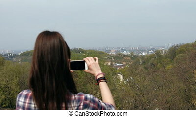 Young woman in checkered shirt taking photo with cell phone at the top of the mountain. View from the back.