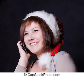 young woman in christmas cap, black background