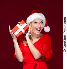 Young woman in Christmas cap hands a gift wrapped with red...