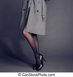 Young woman in coat with beautiful feet