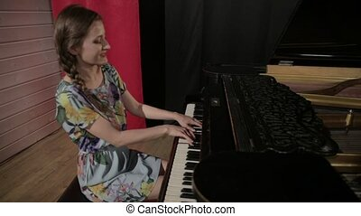 Young woman in color dress playing on the piano