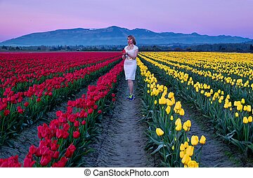 Young woman in colorful tulip fields at sunset.