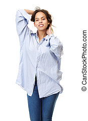 Young woman in comfortable shirt and jeans smiling with hands in hair