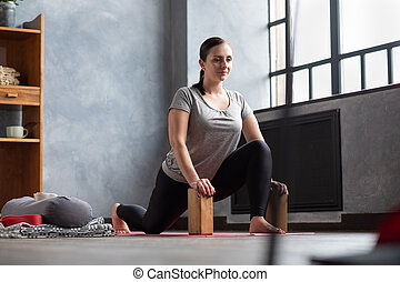 Young woman in comfortable sportswear doing wide lunges stretching legs