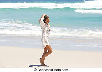 Young woman in contemplation walking on the beach