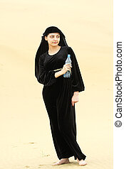 Young woman in desert withh bottle of water