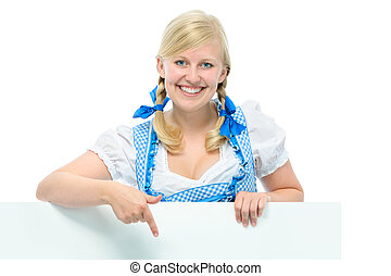 young woman in dirndl holds ad space and smile