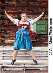 Young woman in Dirndl jumping from