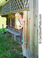 Young woman in dirndl looks out of