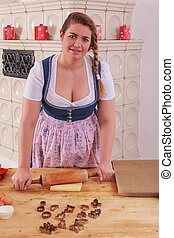 Young woman in dirndl rolling a dou