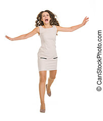 Young woman in dress jumping forward