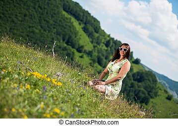 young woman in dress sitting on the grass