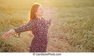 Young woman in dress smiling and raises her hands up while standing in a field of ripe wheat