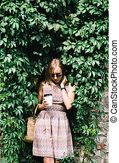 Young woman in dress with coffee to go on green hedge