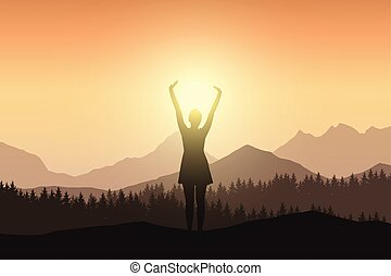 Young woman in dress with raised hands in mountain landscape with forest in sunshine