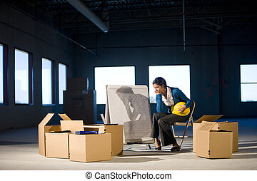 Young woman in empty office space with moving boxes